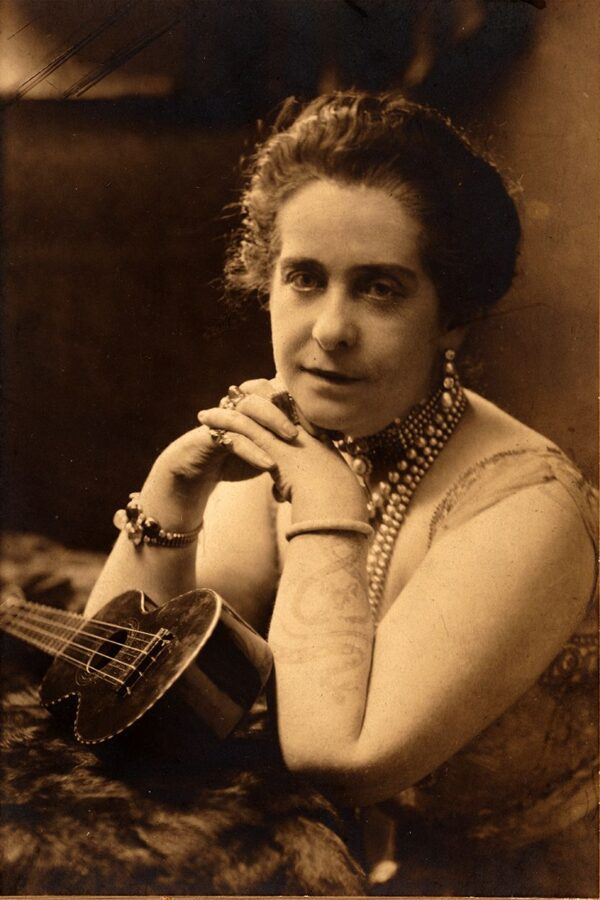A middle-aged white woman poses for a photograph with a ukelele in what appears to be the early 1900s. She wears a lot of jewelry and a sleeveless dress. Her right foreman has a tattoo of intertwining snakes.