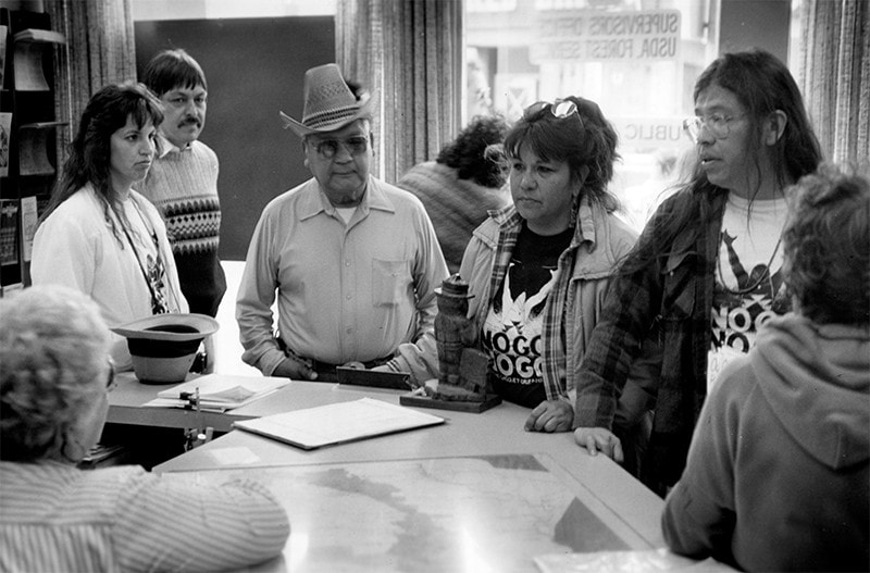 A group of Native men and women gather around a desk.