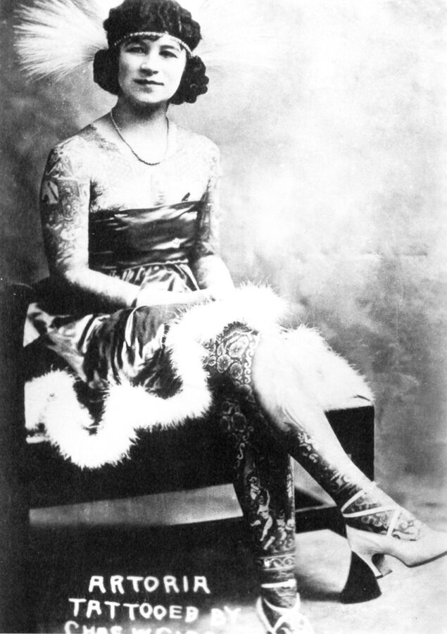 A young white woman sits on a bench with her legs crossed. She is wearing a strapless dress with feathers on the hem, a necklace, and heels. She is completely tattooed from her neckline to her feet.