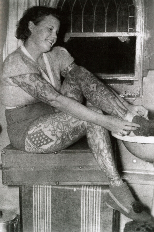A young white woman with fully tattooed legs and arms tattooed to her elbows sits while she puts on a sock.