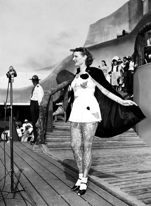 A heavily-tattooed woman stands on stage during a contest. She is wearing a short dress and a cape.