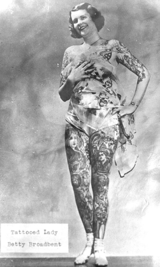 """A young, heavily tattooed white woman stands holding a cloth covering over her chest. In the bottom corner are the words """"Tattooed Lady Betty Broadbent."""""""
