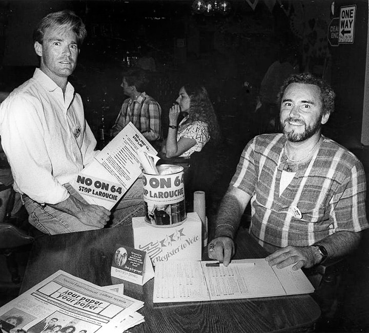 """Two white men look at the camera in a bar. Around them are cans, papers, and flyers saying """"No on 64"""" and """"Stop LaRouche."""""""