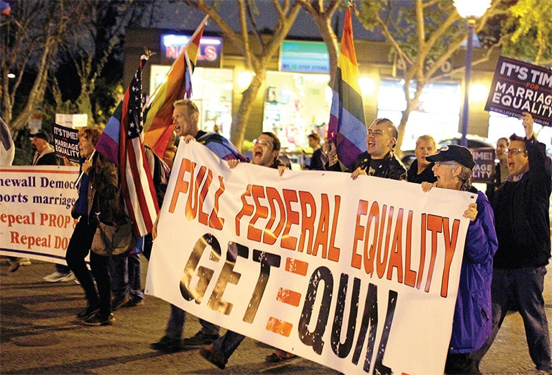 A group of people march down a street carrying rainbow flags, American flags, banners, and signs.