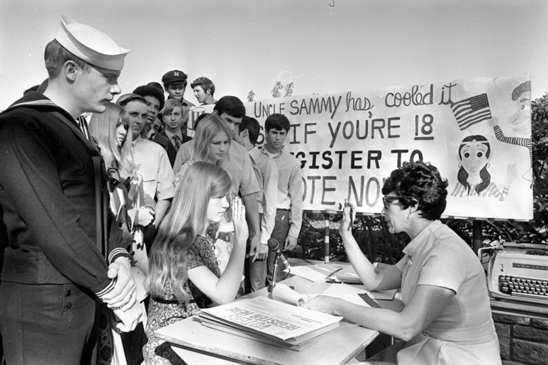 """A group of high schoolers stand behind a girl seated at a table. She is taking an oath before voting. A banner is partially-obscured behind them, but readable parts say """"Uncle Sammy has cooled it. If you're 18 register to vote now."""""""