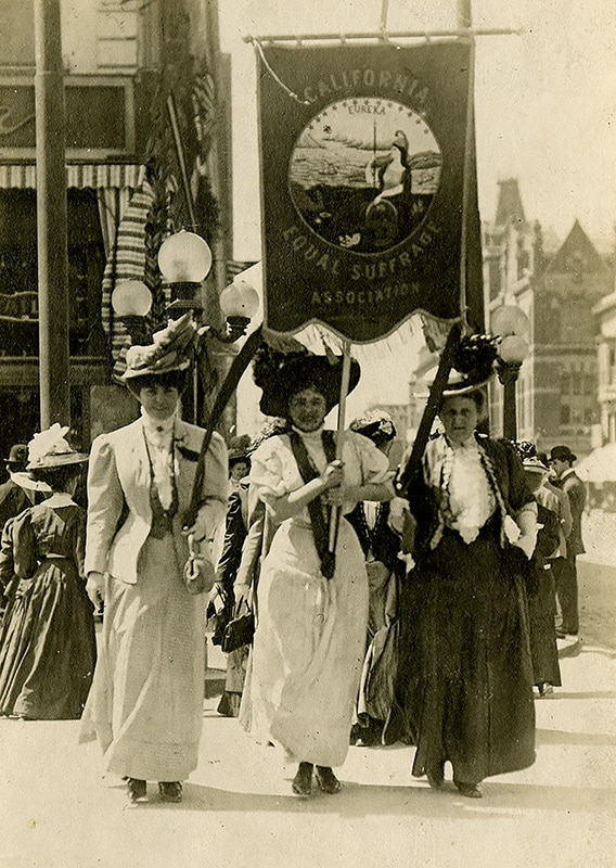 """Three white women march down a street holding a banner that reads, """"California Equal Suffrage Association."""" Other women stand behind them."""
