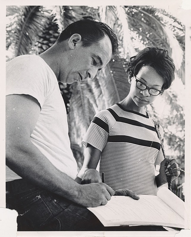 An African American woman registers a man to vote.