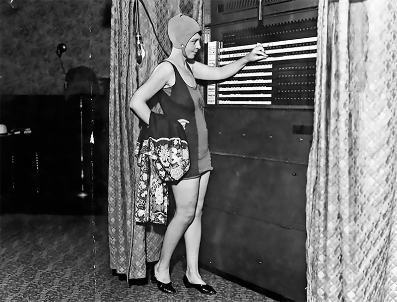A white woman in a bathing suit and shoes places a vote.