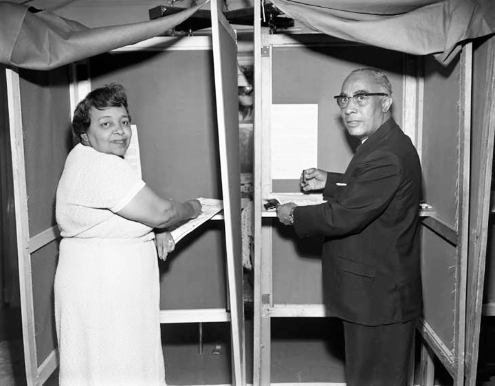 An African American couple vote in voting booths.