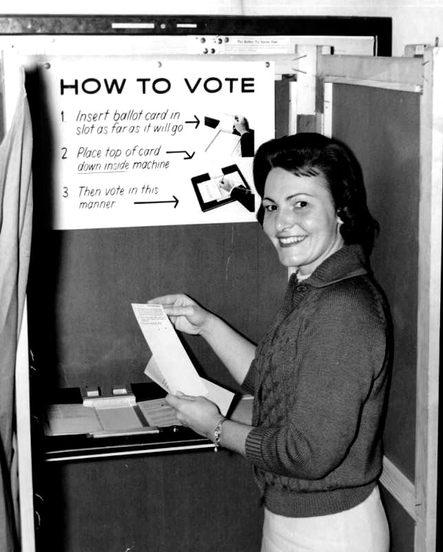 A white woman smiles at the camera as she demonstrates how to use a new voting machine. Instructions for the voting machine are posted behind her.