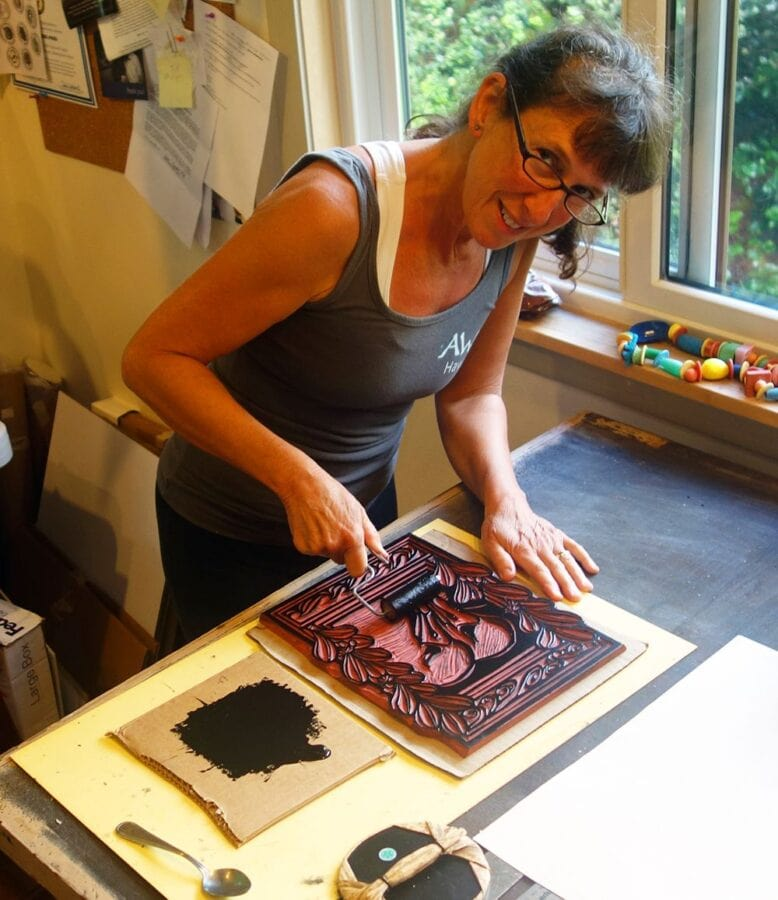 A white woman looks at the camera while rolling black paint onto a wood-cut block.