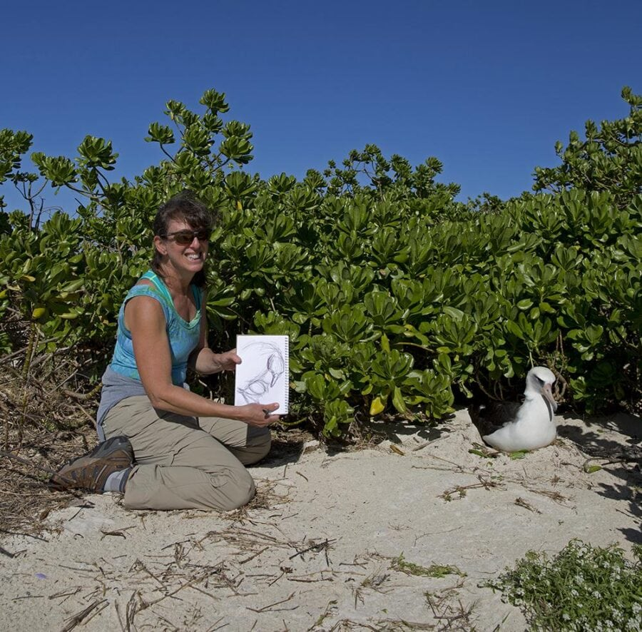 A white woman holds up a notebook with a sketch of an albatross. Next to the notebook is a real albatross sitting on a nest.