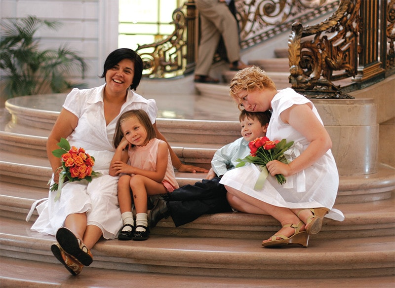 Two women in white wedding dresses sit with their two children on the steps of a grand staircase.