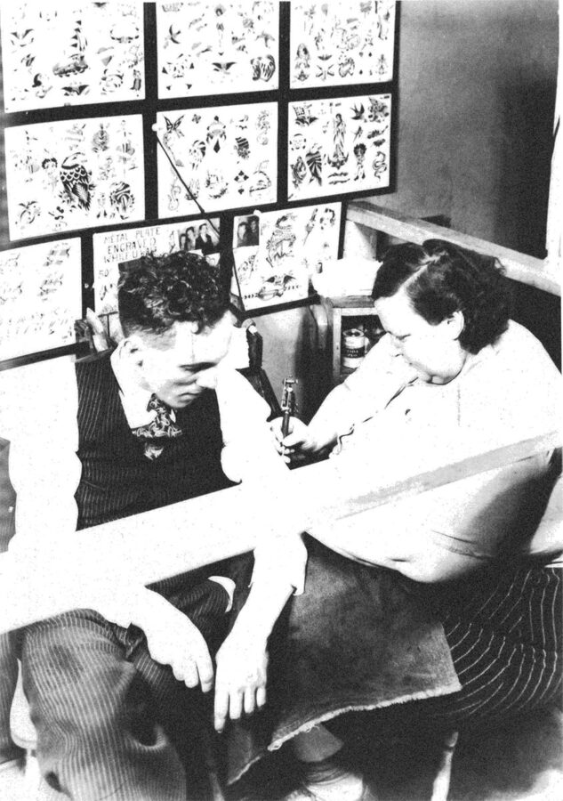 A fat white woman tattoos a thin white man's arm. On a nearby wall are sheets of paper with different tattoo designs.