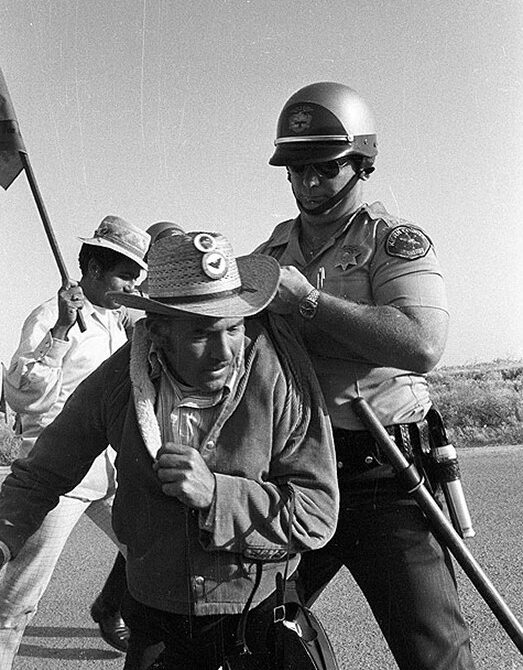 A policeman arrests a Mexican man. The Mexican farm worker is wearing a United Farm Workers pin on his hat.