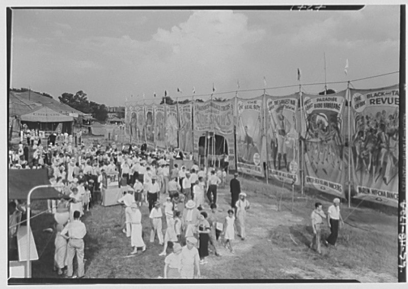 A number of men, women, and children enjoy an outdoor circus. Huge banners are strung up near them, at least three times as tall as the humans in attendance.