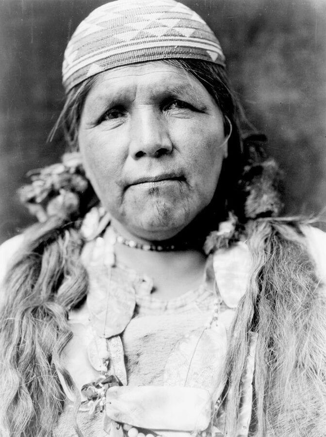 An older Hupa woman wears a basket cap and has faint tattoo markings on her chin.