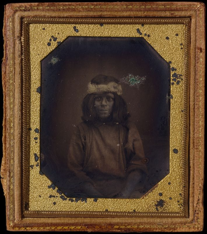 A young Native American boy sits for a portrait.