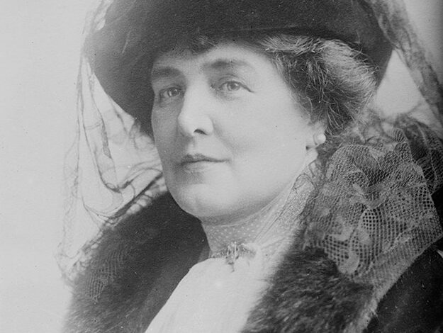 A middle-aged woman wears fine clothes in an old photograph.