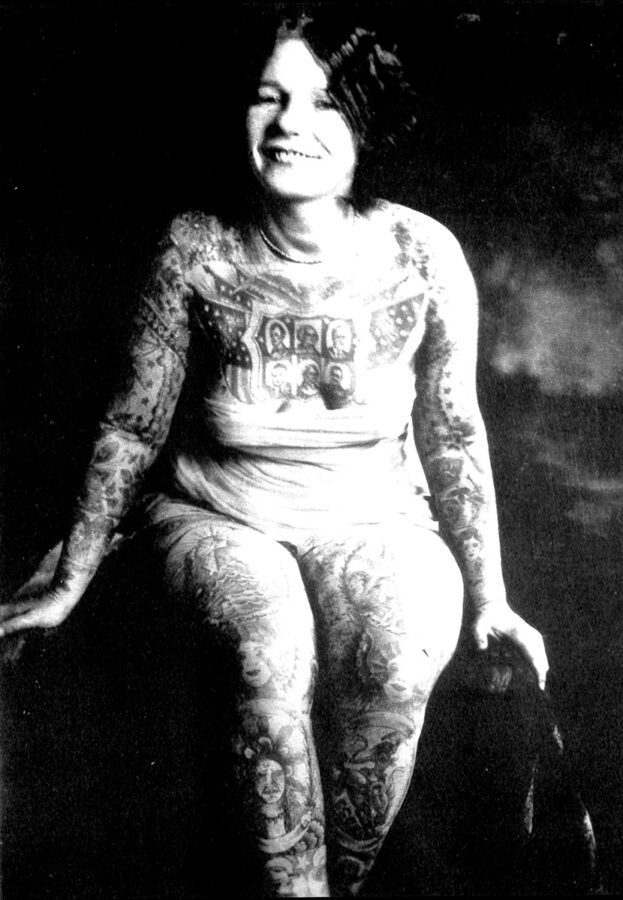 A fully-tattooed young white woman with a bob haircut smiles at the camera as she leans forward in a seated position. She is wearing a bodysuit, and her many tattoos are clearly visible.