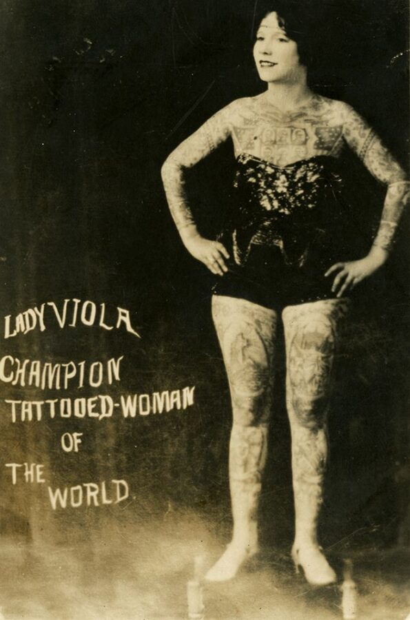 """A heavily-tattooed young white woman wears a sparkly bodysuit and heels. She stands with her hands on her hips and smiles for the camera. The text on the photo reads, """"Lady Viola Champion Tattooed-Woman of the World."""""""