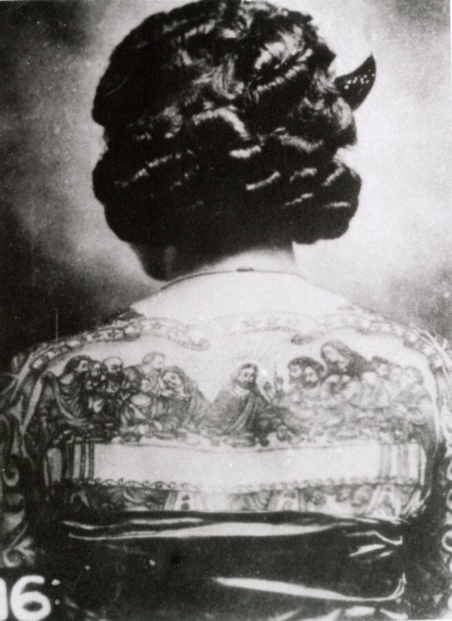 """A woman's back is tattooed with a well-done, large reproduction of """"The Last Supper"""" by da Vinci."""