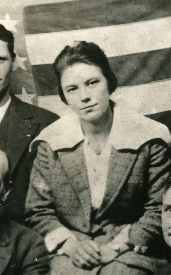 A young white woman sits with her hands clasped in her lap in a group photo, although the photo crops out the other faces. An American flag is used as the photo's backdrop.