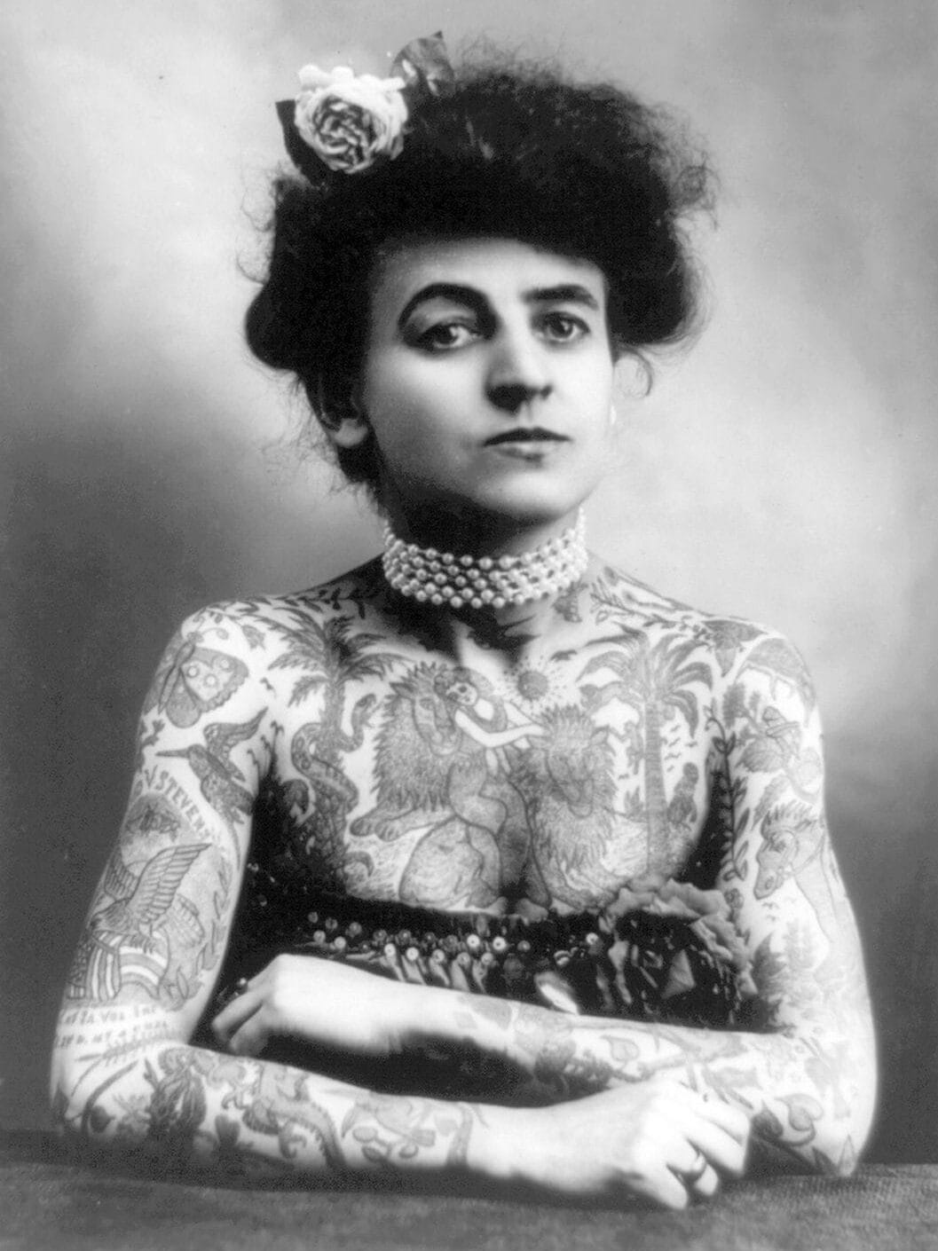 A middle-aged white woman is fully tattooed from her neck to her wrists. She poses with her arms crossed and looks at the camera defiantely.