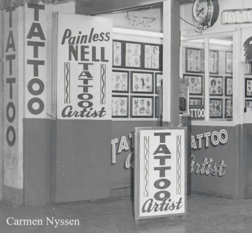 """An exterior of a building shows has the words """"Tattoo"""" and """"Painless Nell Tattoo Artist"""" painted on the walls. Sheets of tattoo flash, pre-drawn designs, are also visible."""