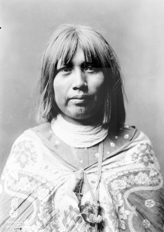 A Mohave woman wears traditional dress in a black-and-white photograph. She has shoulder-length hair and five thin lines tattooed on her chin.