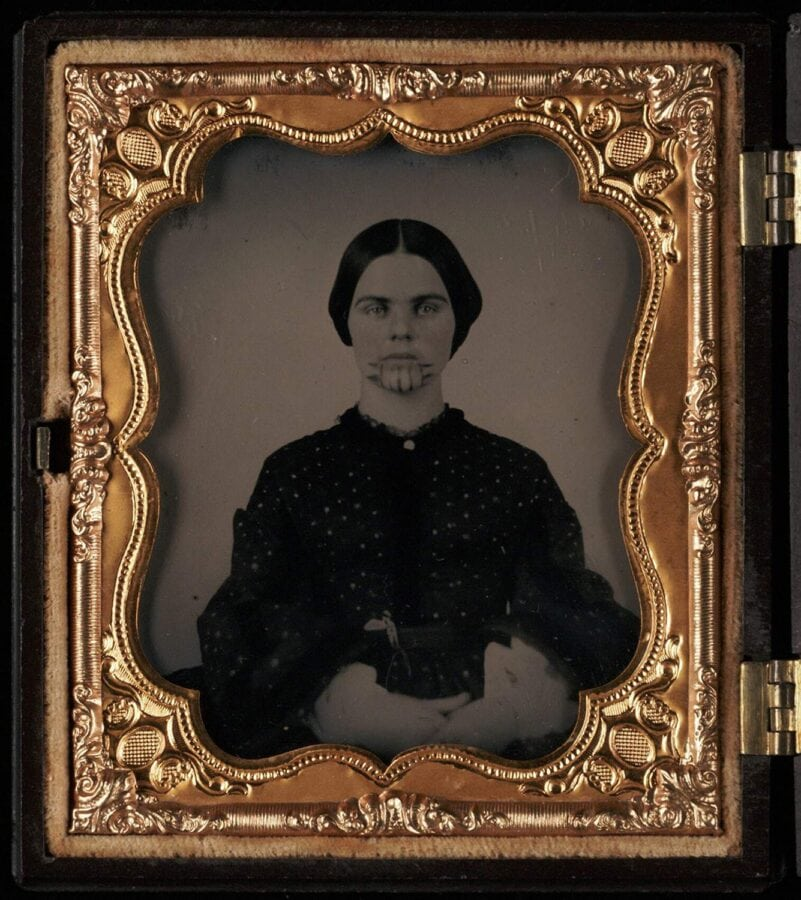A young white woman stares at the camera in an old tintype photo. She has very clear and dark lines tattooed on her chin.