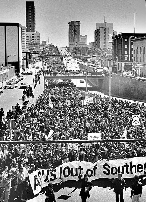A seemingly-unending mass of people march in protest on a wide road in a city.