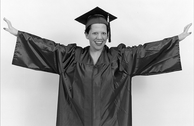 A young woman stands with her arms outstretched, wearing a graduation cap and gown.