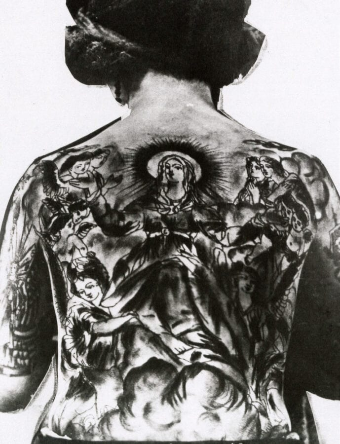 A woman has a large backpiece with the Virgin Mary at its center. Angels flank the Virgin Mary.