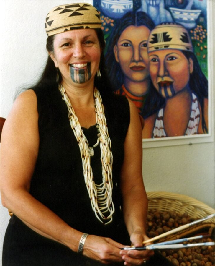 A Native woman wears a shell bead necklace and basket hat. She has three thick black lines as a chin tattoo. A painting showing two Native women, one with a chin tattoo, is behind her.