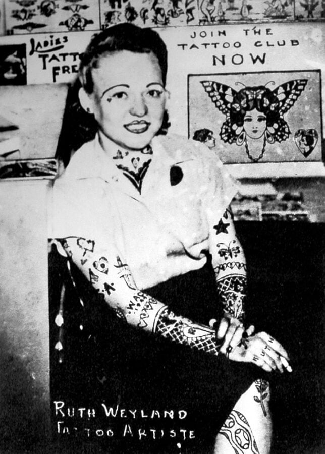 A young woman sits in her tattoo shop with sheets of flash behind her. She appears to have many tattoos.