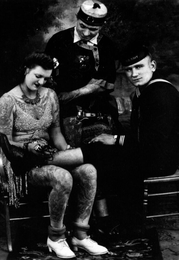 A heavily-tattooed young white woman sit with a soldier's leg in her lap. She is tattooing a design on his shin. Another sailor stands behind them, looking on.