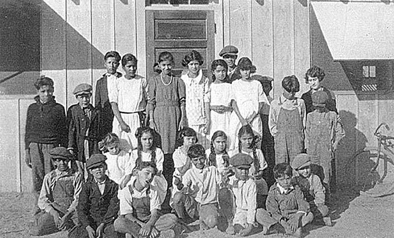 A group of children pose for a class photo outside of a wooden building.