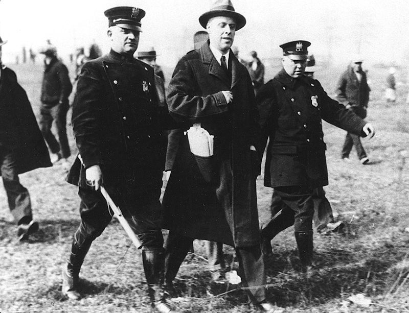 Policemen escort a man in a suit away from a crowd.
