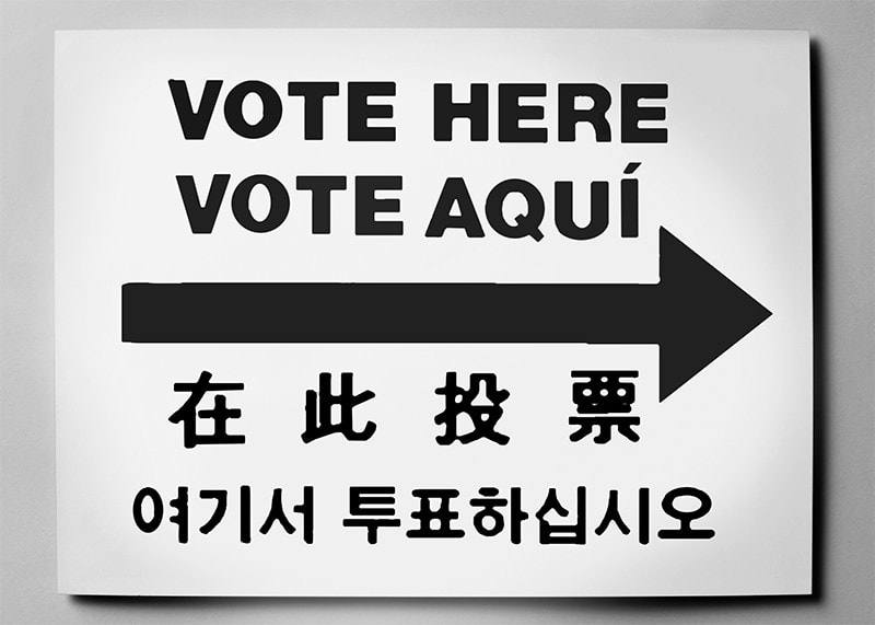 """A sign says """"Vote Here"""" in four different languages."""