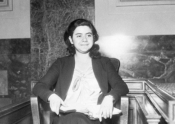 A young woman sits in a chair in what appears to be a courtroom.