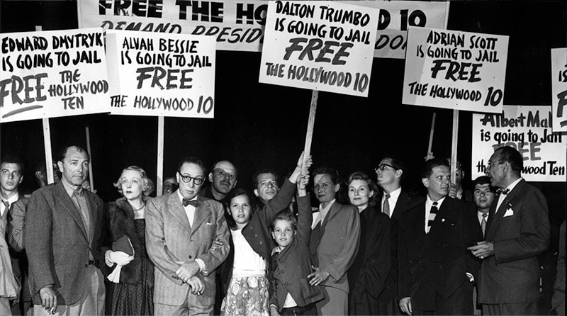 A group of men, women, and children hold picket signs related to freeing the Hollywood 10.