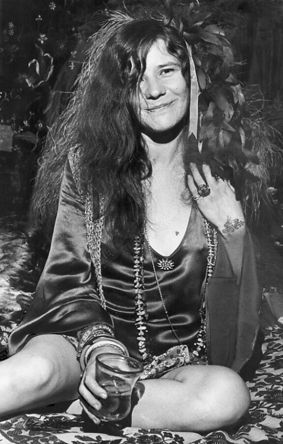 Rock and roll artist Janis Joplin sits with a drink in one hand. A bracelet-like tattoo is visible on her left outer wrist.
