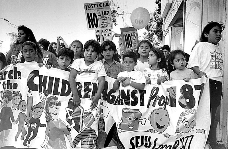 """A group of children hold a banner saying """"Children Against Prop 187."""""""